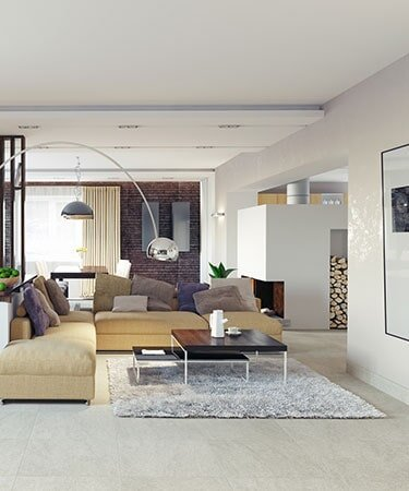 A bright, modern living room with a tan couch, white tile floor, and a large area rug