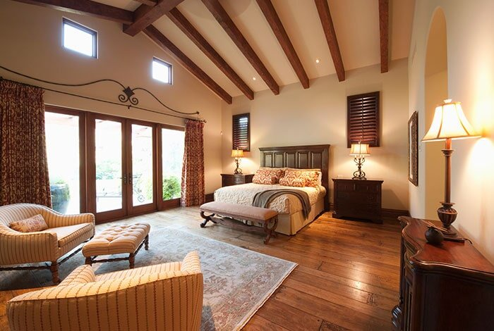 A softly-lit, luxuriously furnished bedroom with a dark wooden floor and large area rug