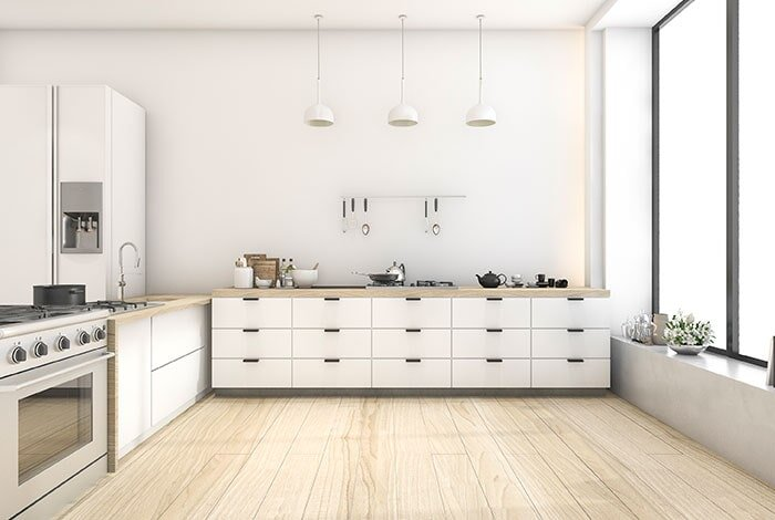 A well-lit open kitchen with white drawers and appliances and very light wood flooring and countertops