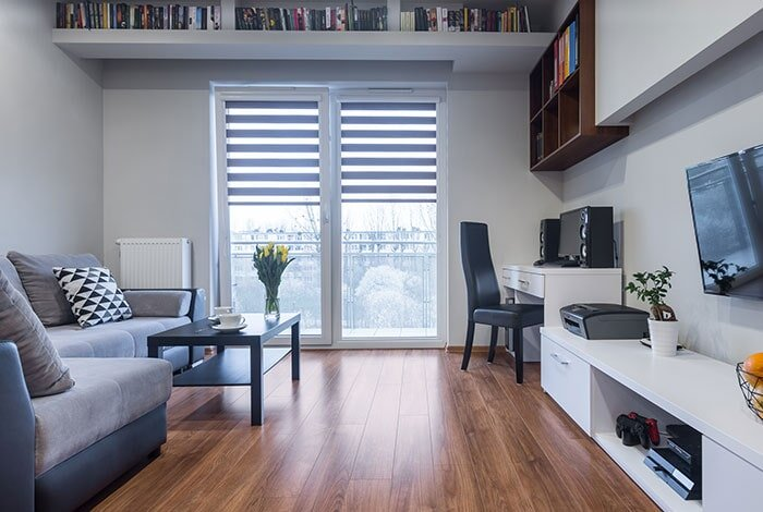 An apartment living room with black and white furniture and a brown wooden floor