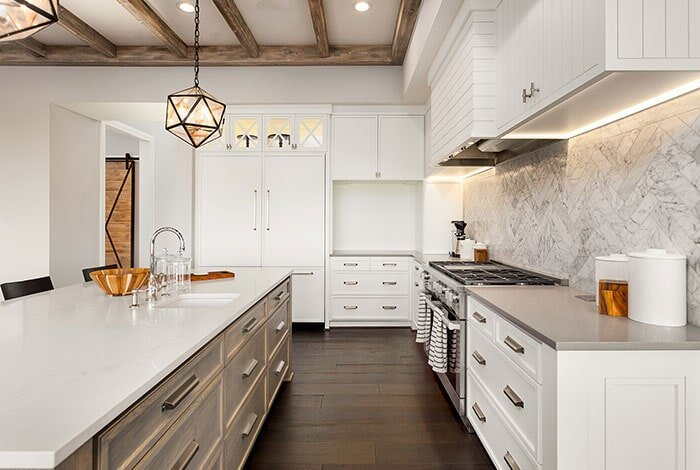 A bright, modern kitchen designed with white countertops, drawers and appliances with a dark wooden floor