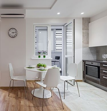 A modern kitchen/dining room combination with white furnishings, white tile floor and light brown wooden floor