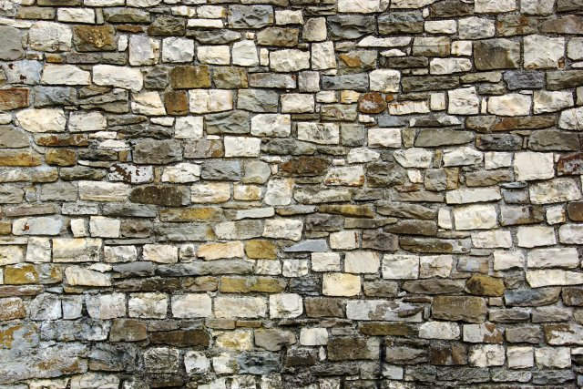A natural stone wall made up of various shapes and colors of stone