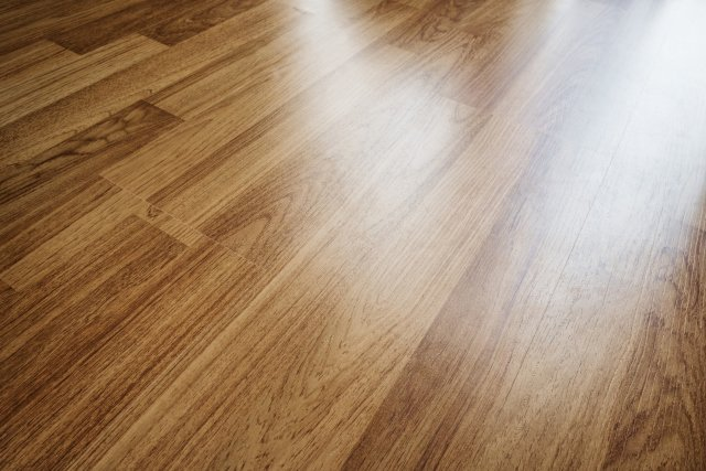 Light wood grain floor that is reflecting bright light