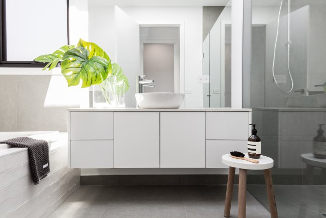 A modern bathroom with a white sink, drawers, bathtub and floor with a big green leafy plant on the counter