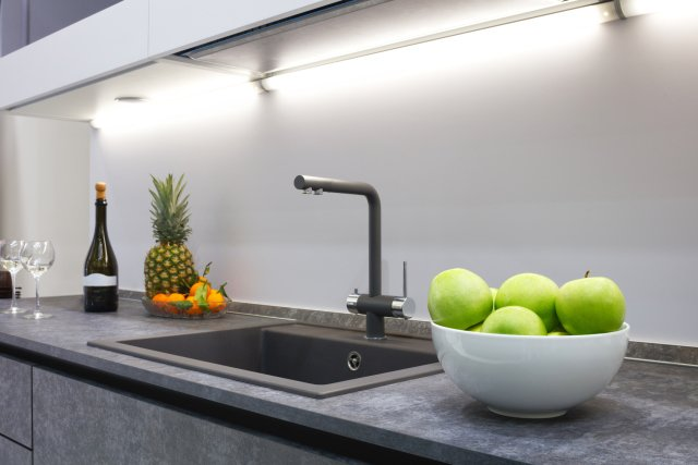 Kitchen sink area with dark grey countertop and various fruits