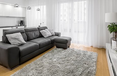 A room a dark grey couch on a light brown wooden floor with a light grey area rug