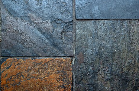 Rectangular-cut Natural Stone with several dark colors and a reddish-brown color