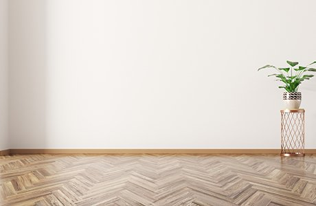 A vinyl floor in a unique pattern that looks like light brown wood below a white wall