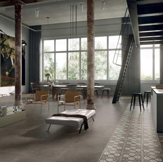 Large open contemporary space with a high ceiling, large windows and a grey tile floor