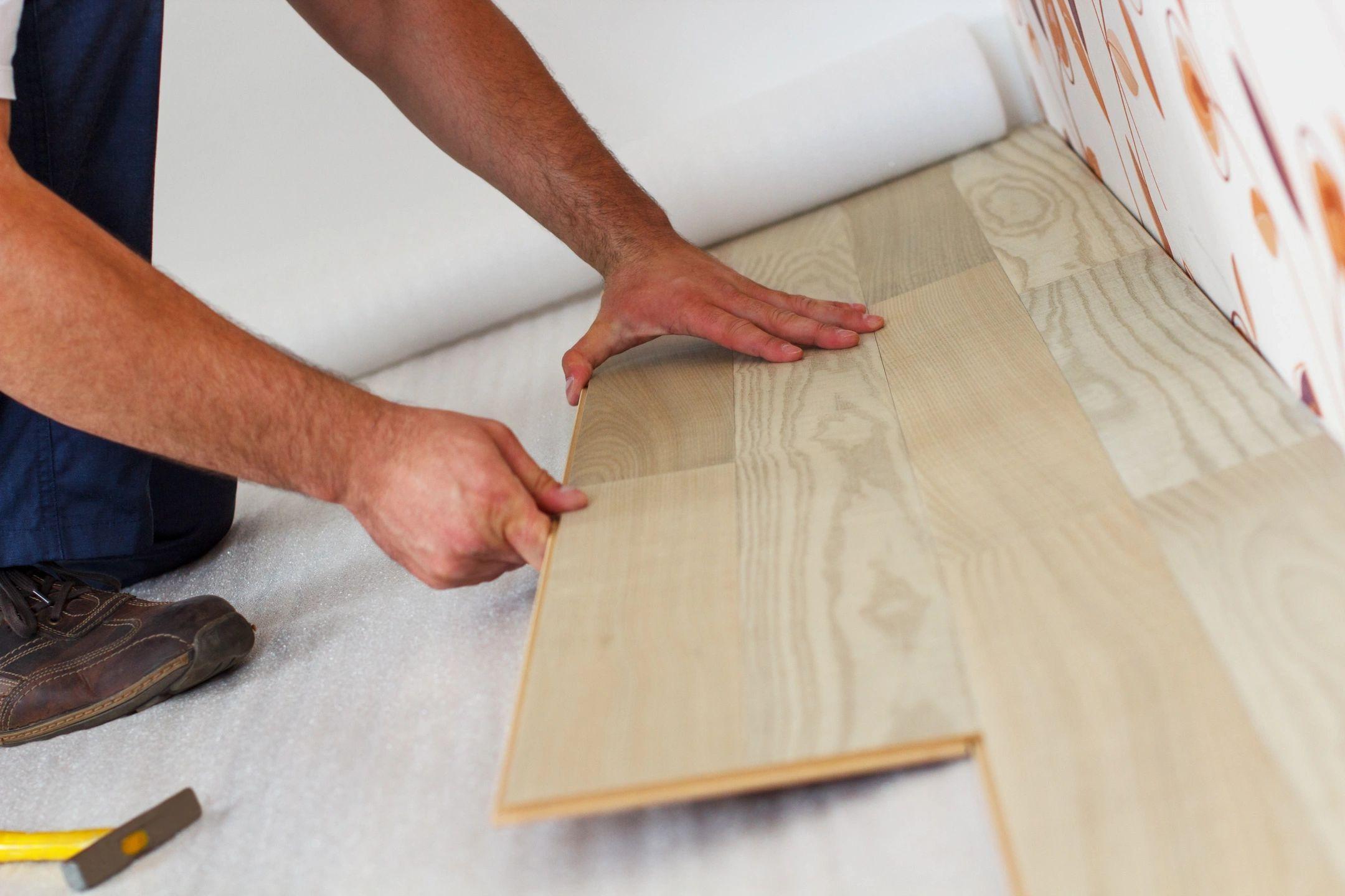 Light brown wood grain vinyl plank flooring being installed