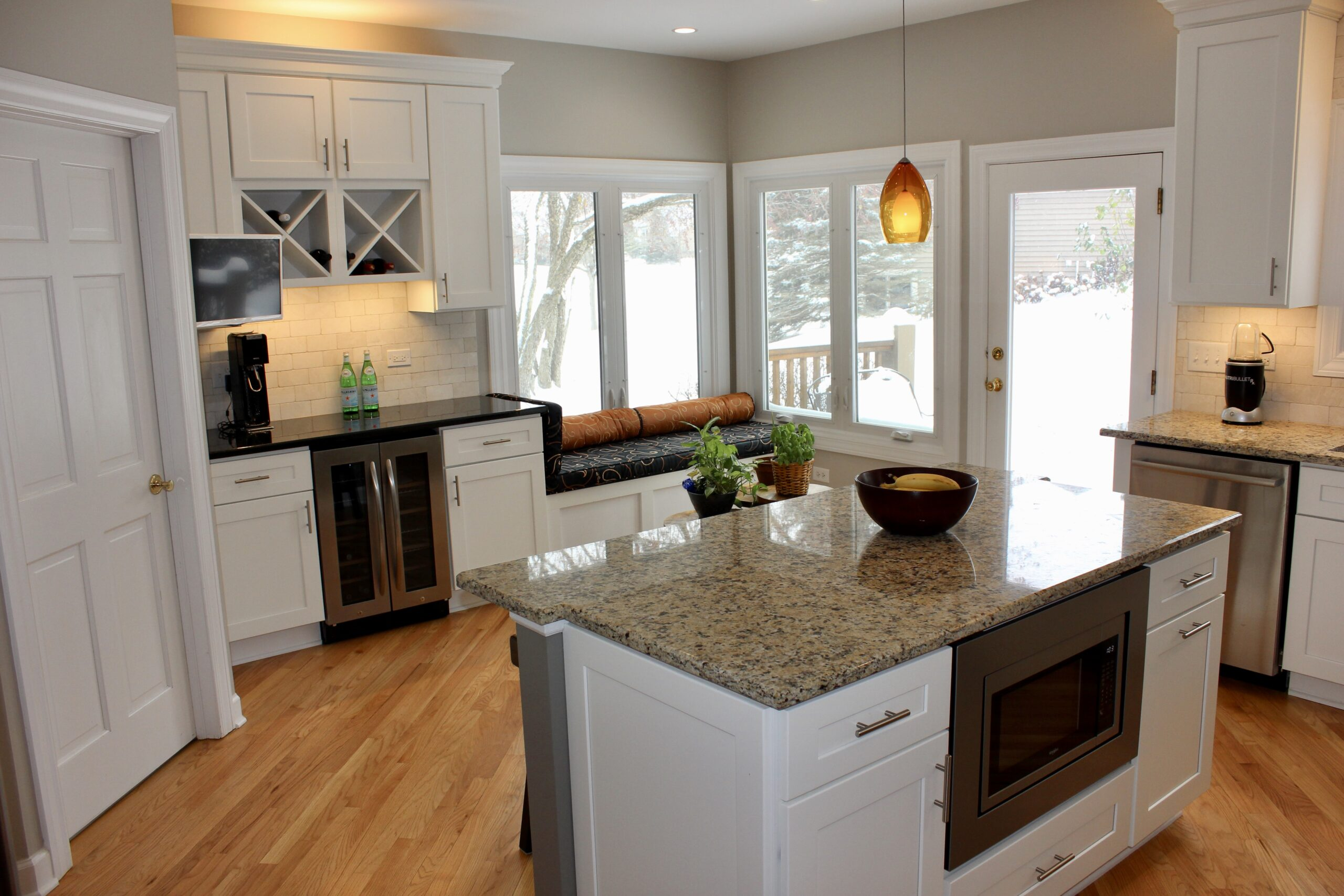 Custom kitchen with granite countertops, wod flooring and stainless appliances