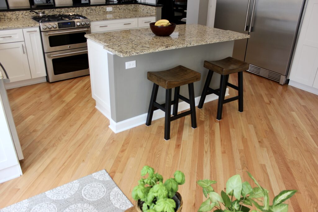 Kitchen with light wood flooring and matching granite countertops