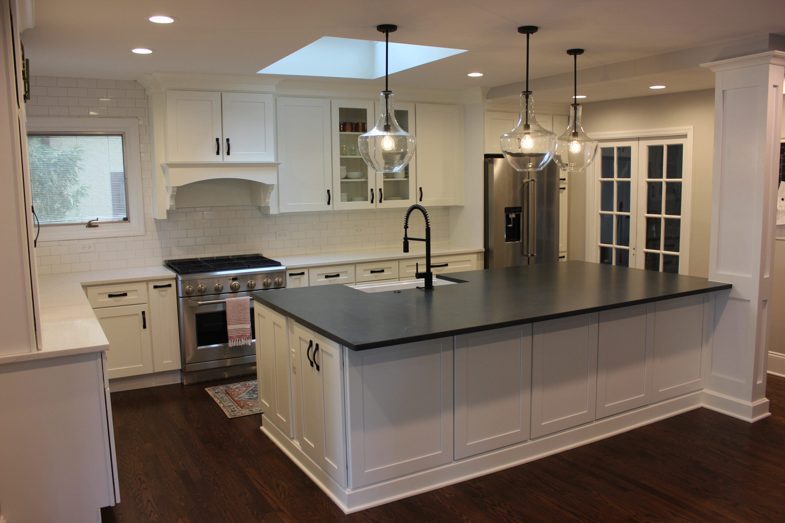 Full view of kitchen with what cabinets and black accents with dark wood flooring