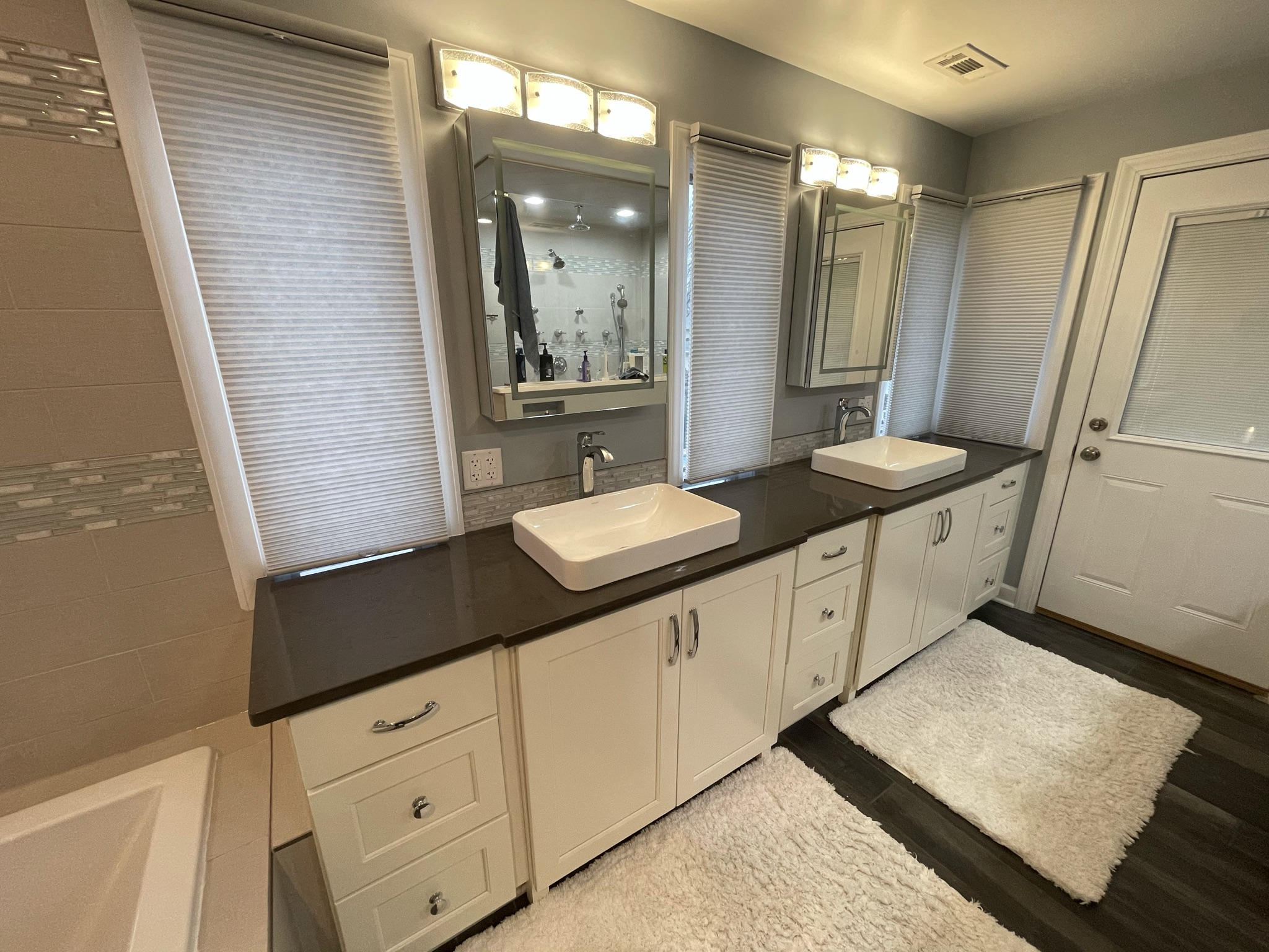 Custom vanity with black countertop, white double sinks and white cabinets